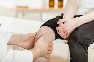 Doctor examining knee of injured minor