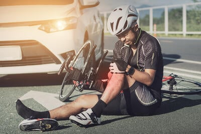 man holding knee in pain after a bicycle crash
