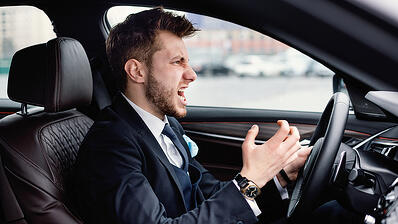 angry driver in a suit behind the wheel of a car