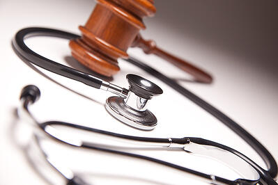 gavel and stethoscope intertwined together